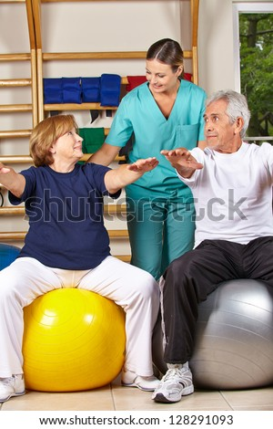 Two senior people doing back fitness training with physiotherapist - stock photo