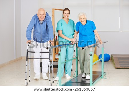 Two senior people doing walking exercise in physiotherapy with physiotherapist - stock photo