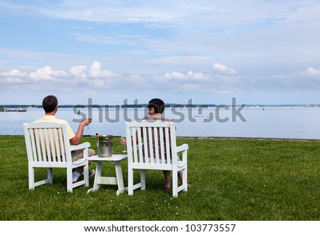 Two senior people in patio chairs drinking champagne by Chesapeake bay - stock photo