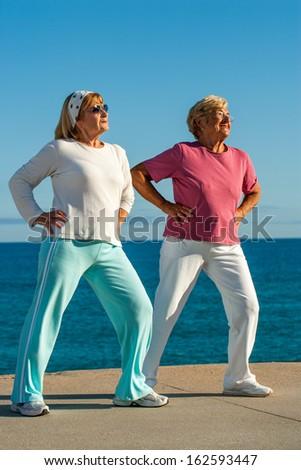 Two senior women doing leg stretching exercise at seafront. - stock photo