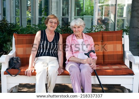 Two senior women enjoying a day outdoors sitting together on a wooden garden bench having a chat and smiling at the camera - stock photo