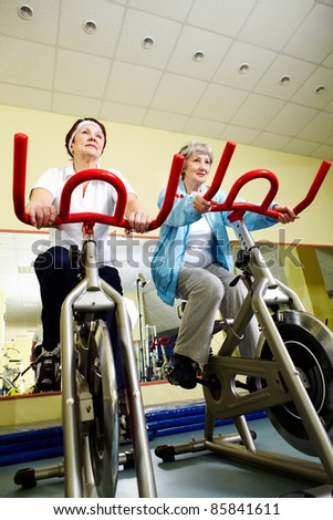 Two senior women practicing on exercise bicycles in gym - stock photo