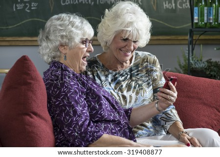 Two senior women sitting on a couch looking at a cell phone - stock photo