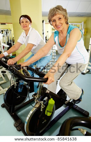Two senior women training actively on exercise bicycles - stock photo