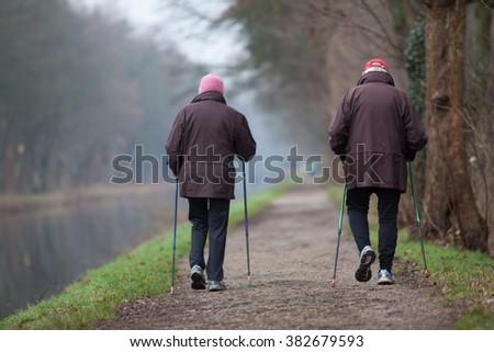 Two seniors are Nordic Walking - stock photo