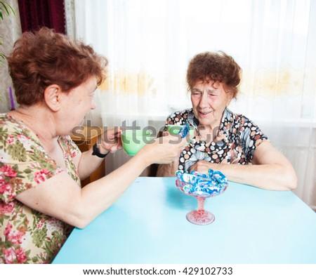 Two seniors drinks tea. Old woman talking. Friendship elderly - stock photo
