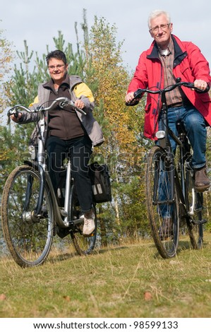 Two seniors on a bicycle trip during summer - stock photo