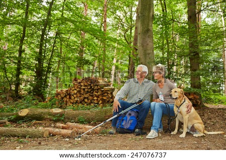 Two seniors on a hike with dog in a forest taking a break - stock photo