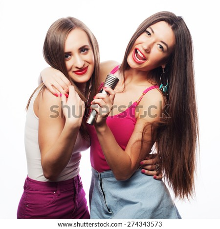 Two sensual girls singing with microphone, isolated on white  - stock photo