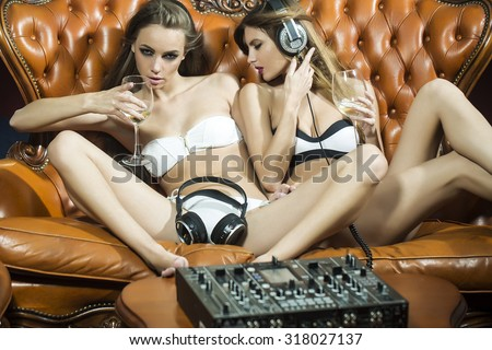 Two sensual young glamour dj women with bright make-up in underwear and headphones sitting on brown leather royal sofa at table with mixer console in night club indoor, horizontal picture - stock photo