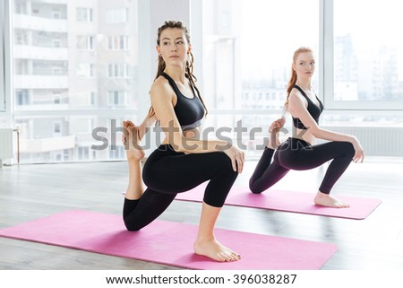 Two serious beautiful young women stretching legs in yoga center - stock photo