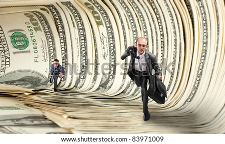 Two serious businessmen running in dollar tunnel - stock photo