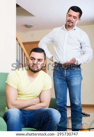 Two serious male adults arguing about something indoors after quarrel - stock photo