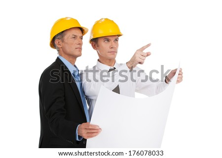two serious older man standing. engineer showing foreman building plan - stock photo