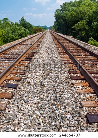 Two sets of railroad tracks run parallel toward the horizon in rural Indiana. - stock photo