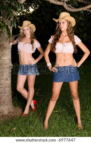 two sexy farm girls standing in field - stock photo