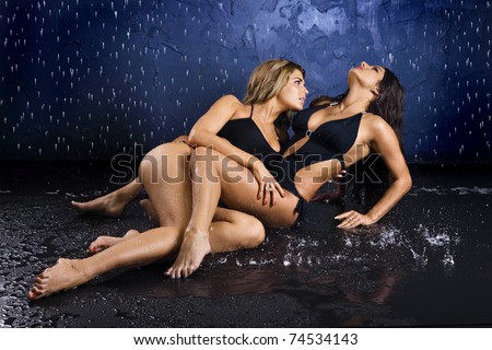 Two sexy girls in bathing suits embrace in water splashes - stock photo