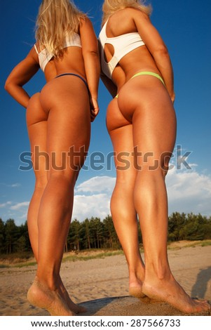 Two sexy girls posing on the beach. - stock photo