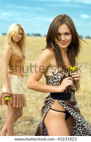 Two sexy women in the field. Focus on brunette - stock photo