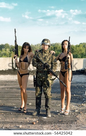 Two sexy women in underclothes leaning on soldier`s shoulders - stock photo