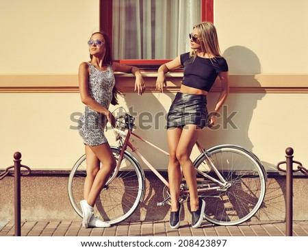 Two sexy women with vintage bike. Outdoor fashion portrait  - stock photo