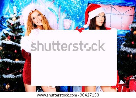 Two sexy young women in Christmas clothes holding white board over Christmas background. - stock photo