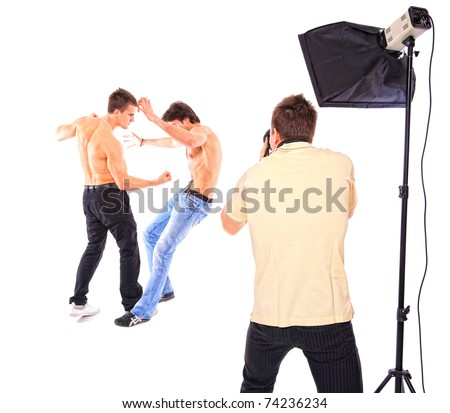 Two shirtless men fighting in studio white photographer is taking pictures over white background - stock photo