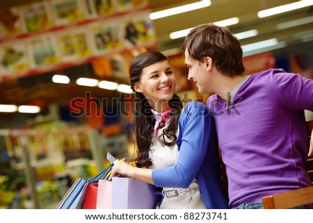 Two shopaholics chatting after good shopping in the mall - stock photo