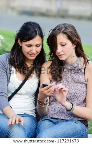 Two shopping girls in park with a mobile phone, - stock photo