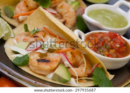 Two shrimp tacos with salsa, guacamole, beer, garnished with mini bell pepper and lime. - stock photo