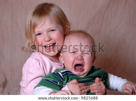 Two siblings - older sister and baby brother - stock photo