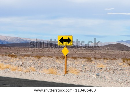 two sided black and yellow road sign designating two way traffic, in desert - stock photo