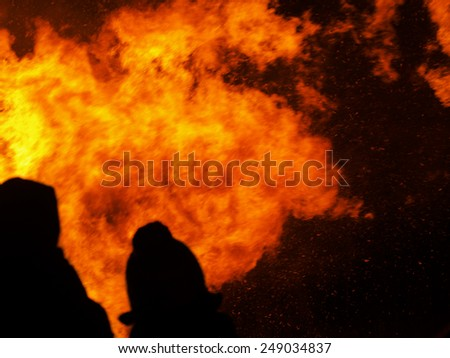 Two silhouetted people, bystanders watch the fire rage.Flames, burning inferno. - stock photo