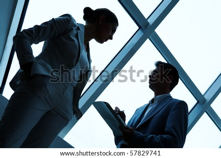 Two silhouettes of businesspeople interacting with each other in the office - stock photo