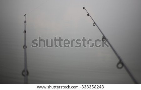 Two similar spinning wobbler fishing rods in natural background of water recreational male hobby vacation spring season, horizontal picture  - stock photo