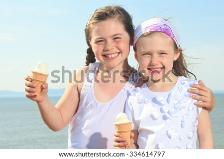two Sister eating ici-cream in front of ocean - stock photo