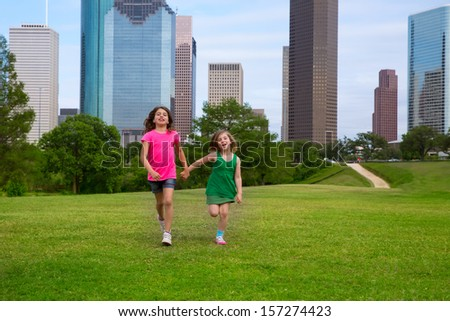 Two sister girls friends running holding hand in urban modern skyline on grass lawn - stock photo