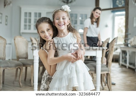 Two sister posing with her mother in a stylish interior - stock photo