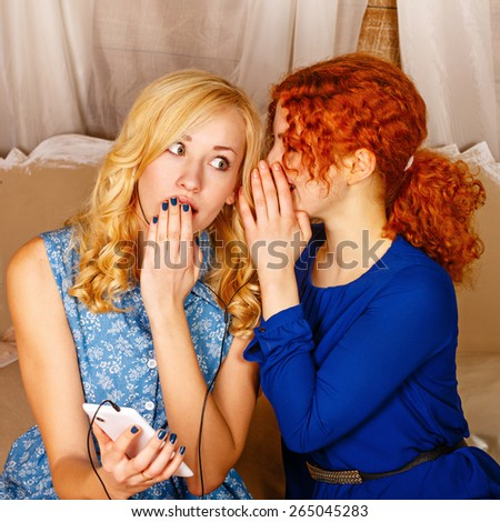 Two sisters, a blonde and a redhead, listening to music on headphones. Girls share the latest secrets, holding a cell phone. Sisters sitting in the bedroom. - stock photo