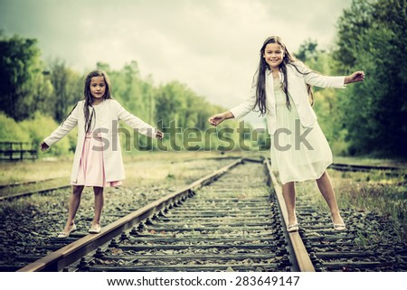 two sisters balancing on a railroad track, vintage effect added - stock photo