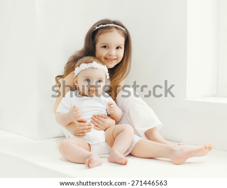 Two sisters children playing together at home in white room  - stock photo