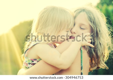 Two sisters Cuddled up together. Back lighting sunlight. - stock photo