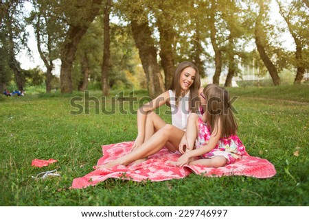 Two sisters enjoy beautiful day in park - stock photo