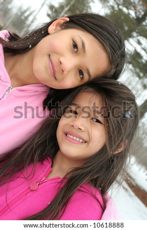 Two sisters enjoying the outdoors in winter - stock photo