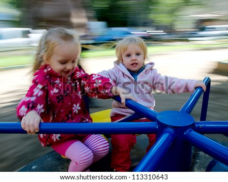 Two sisters having fun on a carousel. Photo with motion blur. - stock photo