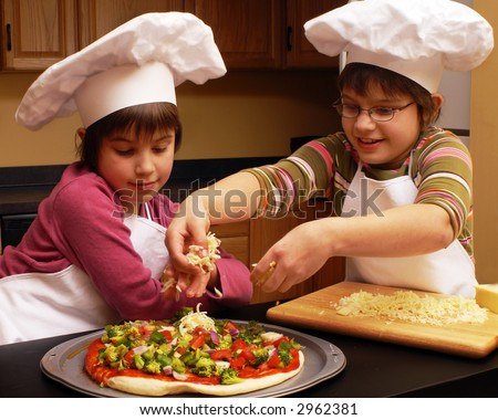 Two sisters in aprons and chef's hats making a veggie pizza. - stock photo