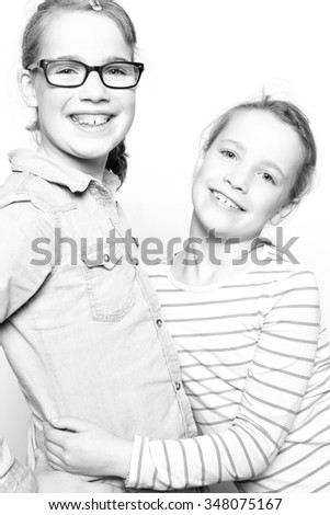 Two sisters  in front of white background - stock photo