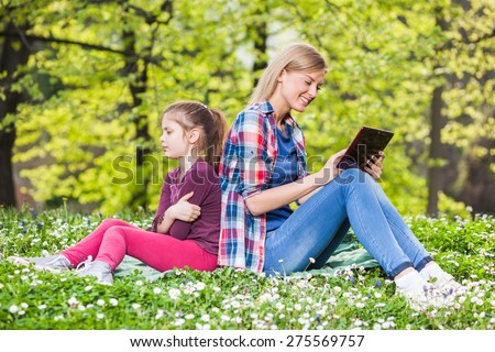 Two sisters in park, older sister is using digital tablet and younger is angry - stock photo