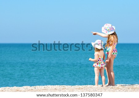 Two sisters look into the distance at sea - stock photo