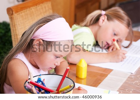 Two sisters, one preschooler drawing, the older one doing homework for school - stock photo